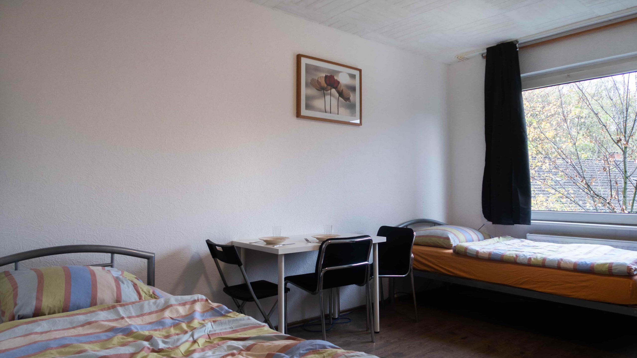 monteurzimmer zwei betten mit tisch im zimmer